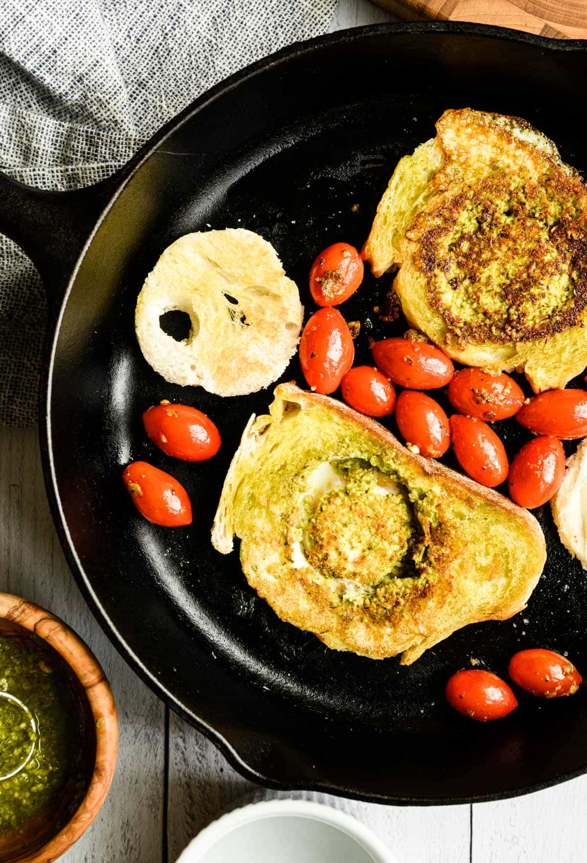 toasted bread with egg in the middle and some cherry tomatoes in a skillet