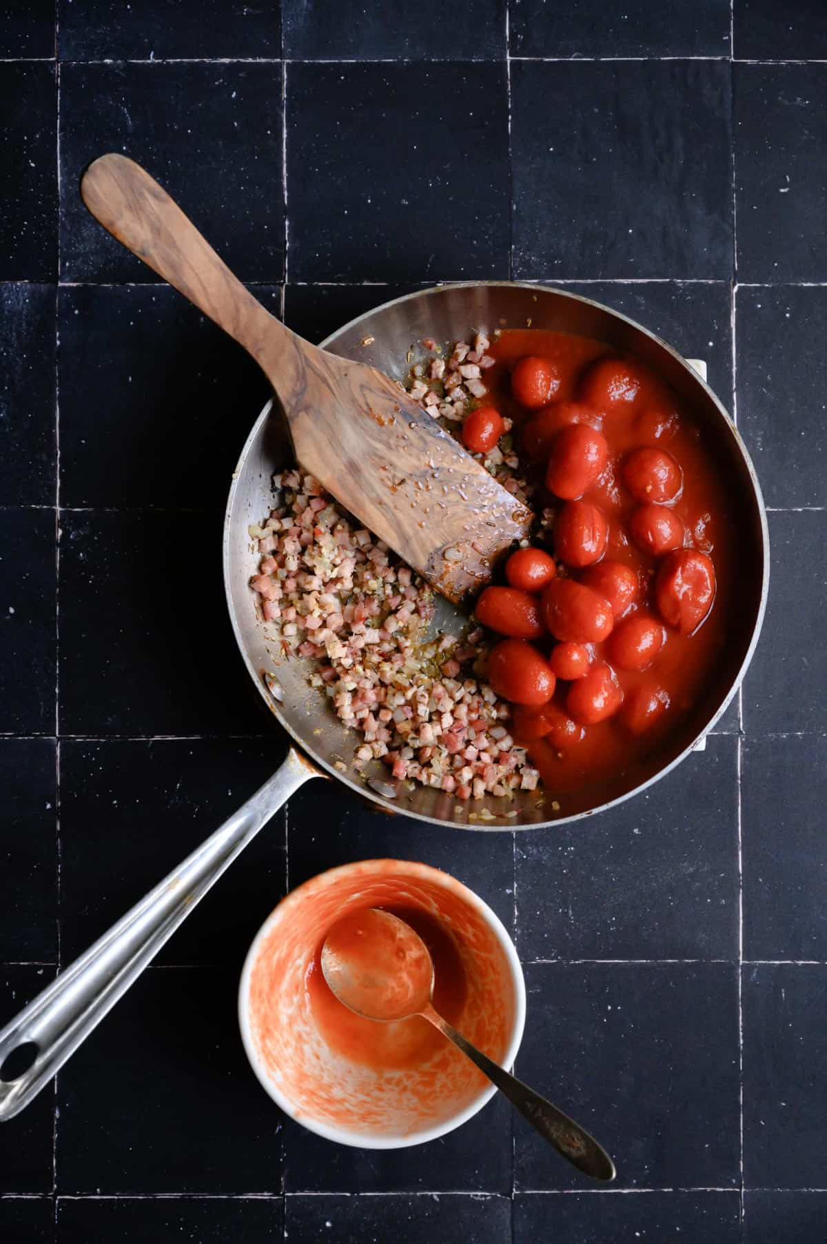 skillet with tomatoes and prosciutto and a wooden paddle