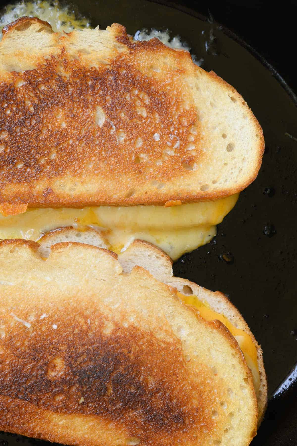 two grilled cheese sandwiches being cooked in a black skillet