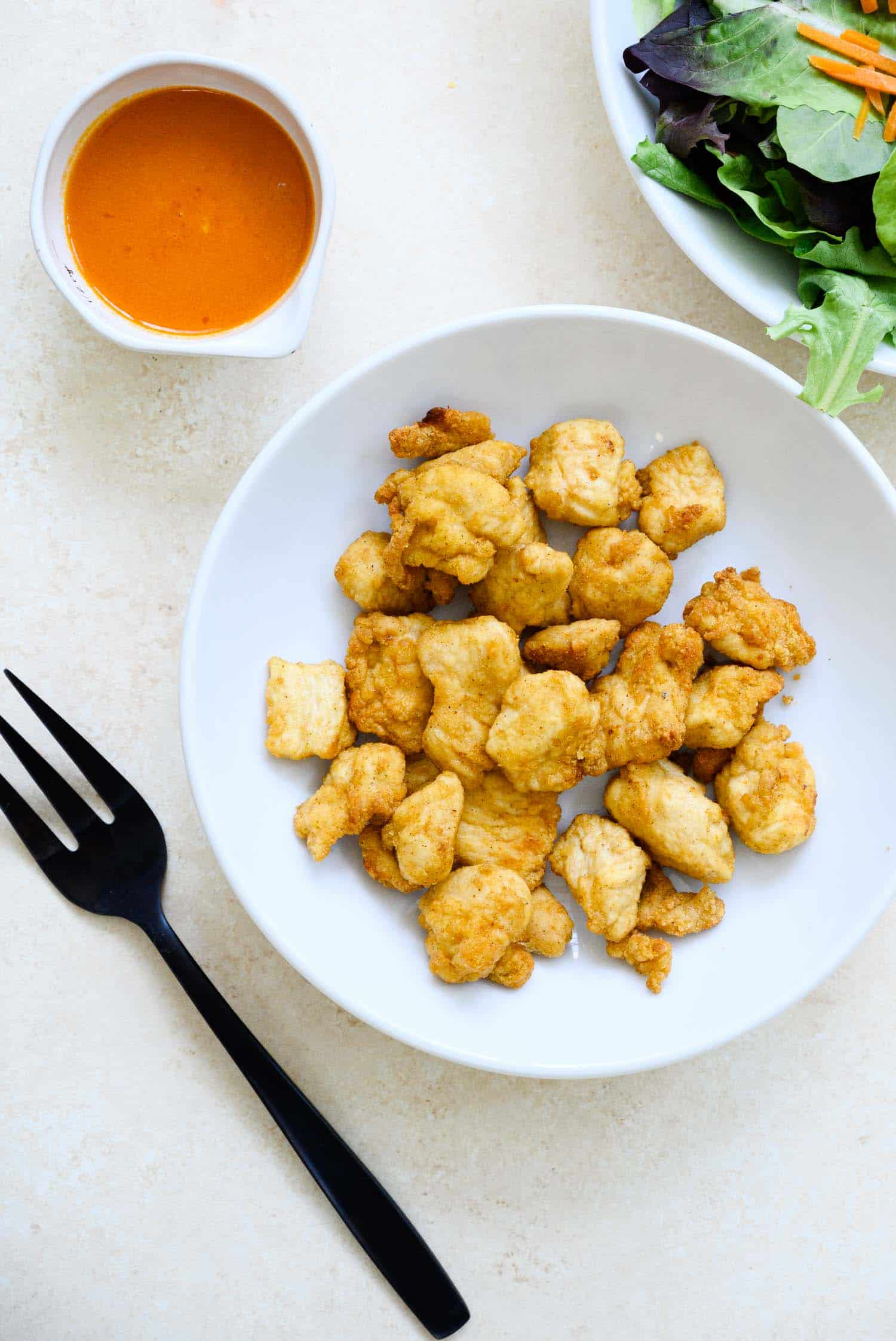 air fried chicken nuggets in a white bowl with a small bowl of Buffalo sauce and a black fork