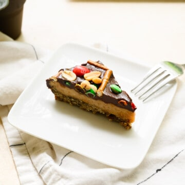 triangle piece of peanut butter pie on a white plate with ganache, pretzels and candy on top