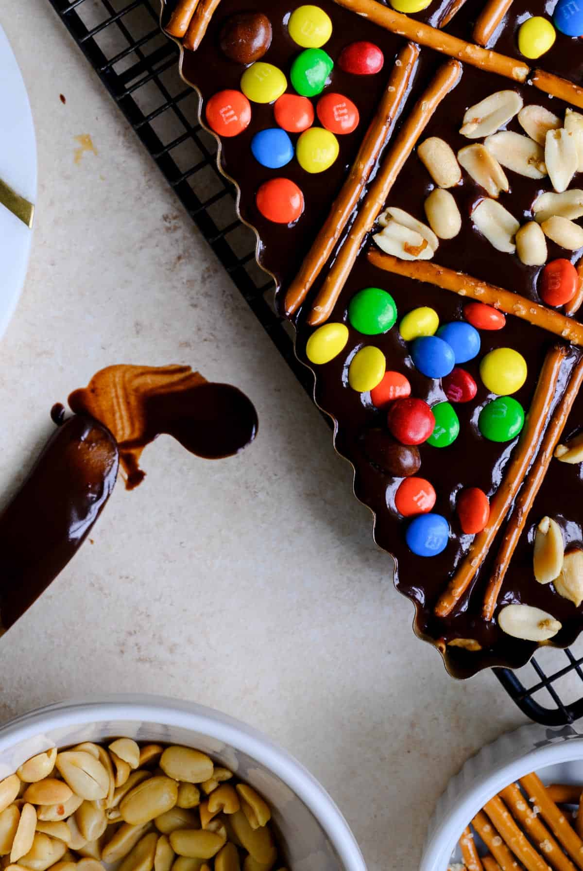 ruffled edge tart pan with chocolate ganache,pretzels, and candy on top with white bowls of pretzels and peanuts