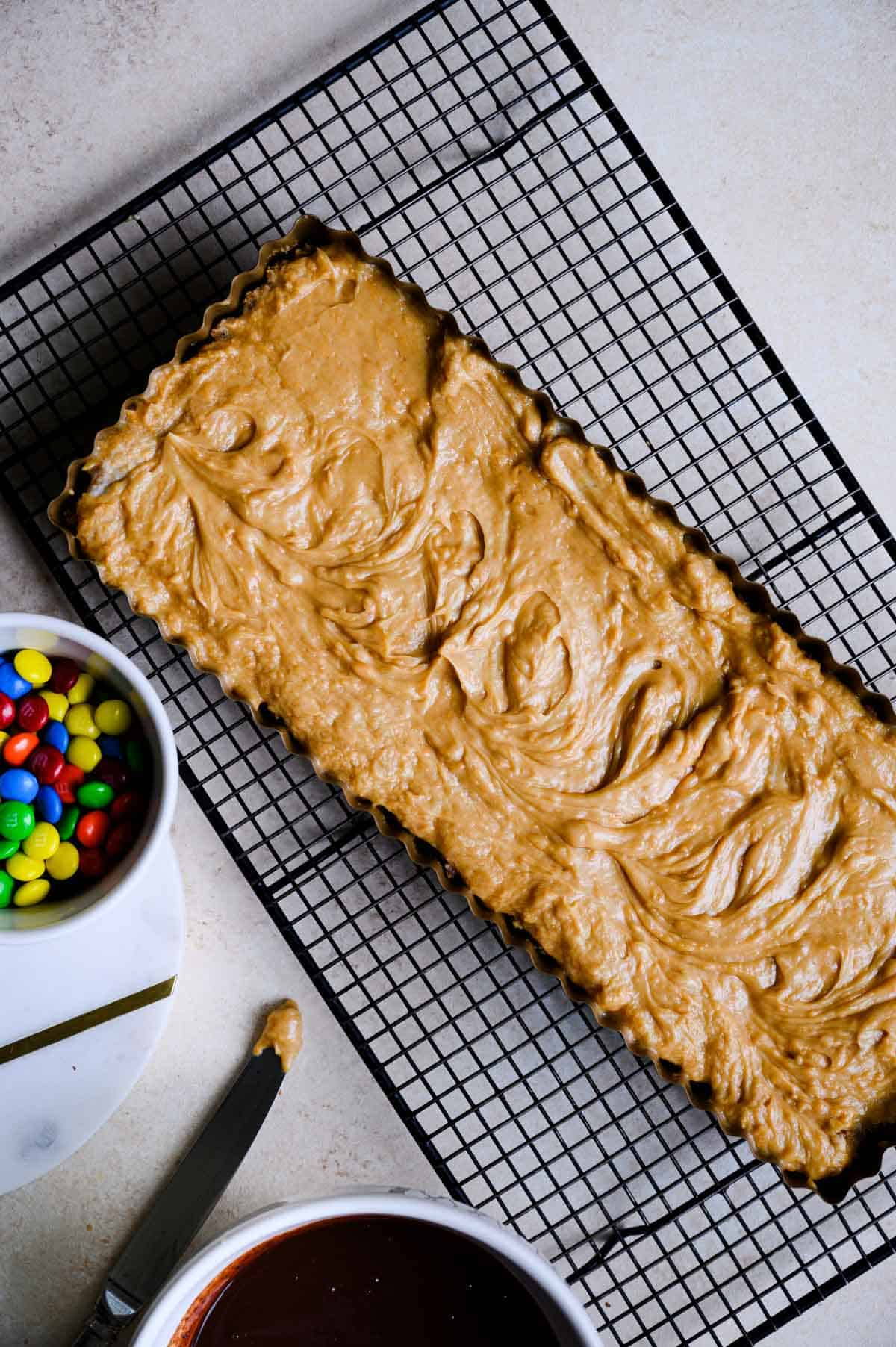 peanut butter mousse filled rectangular tart pan on a black wire cooling rack