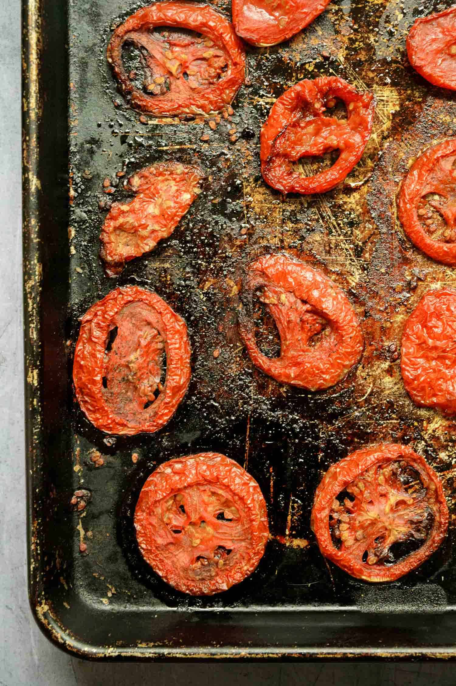 sliced and roasted tomatoes on a darkened sheet pan