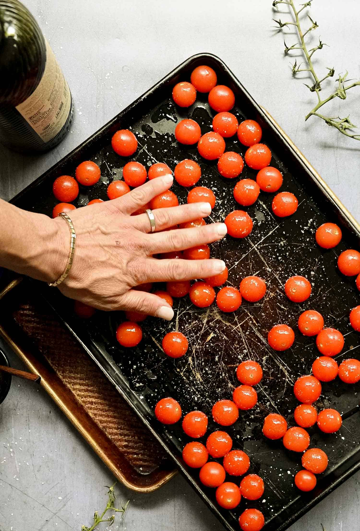 hand rolling cherry tomatoes on an oiled sheet pan