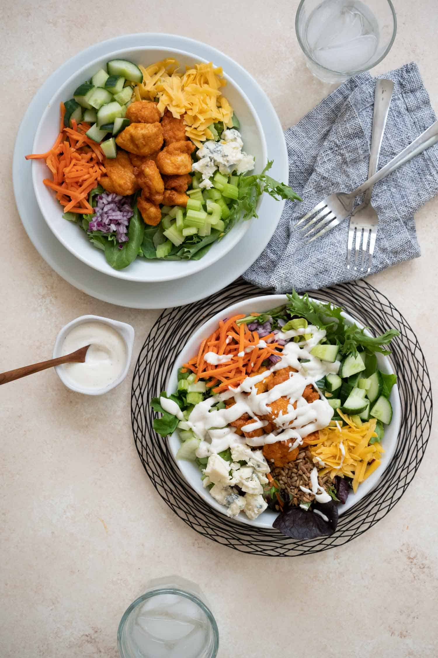 white bowl with big salad of fried chicken and vegetables on a black wire placemat
