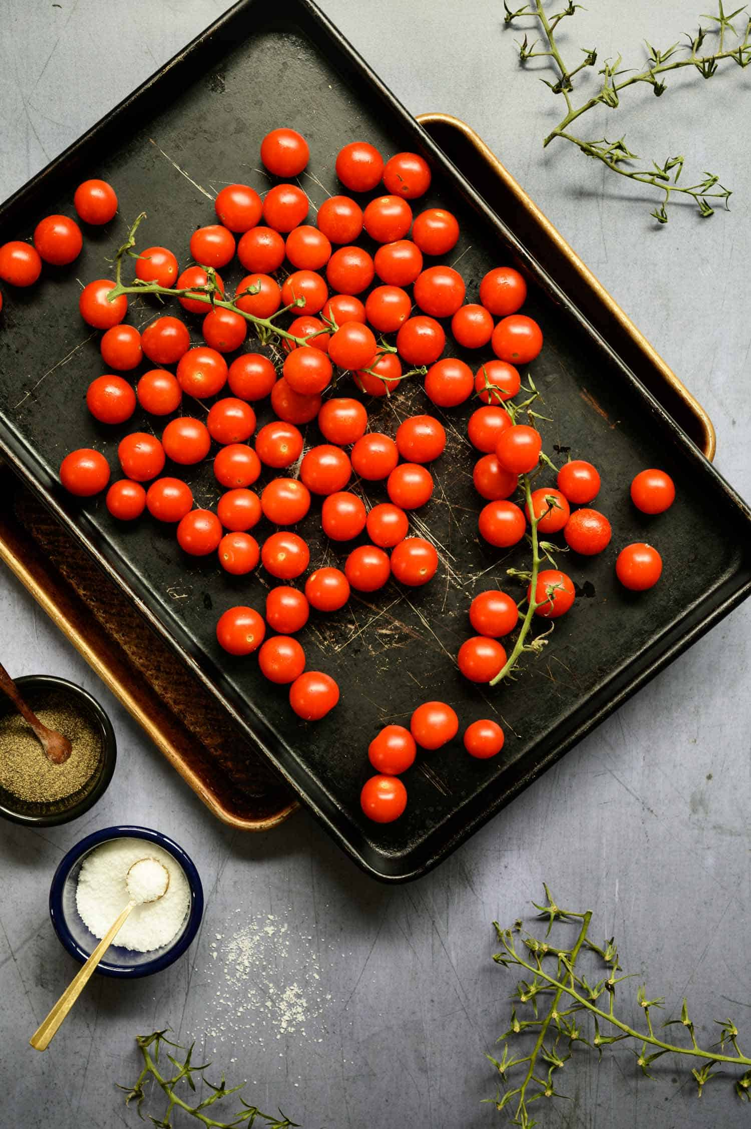 cherry tomatoes on a vine on sheet pans with salt and pepper