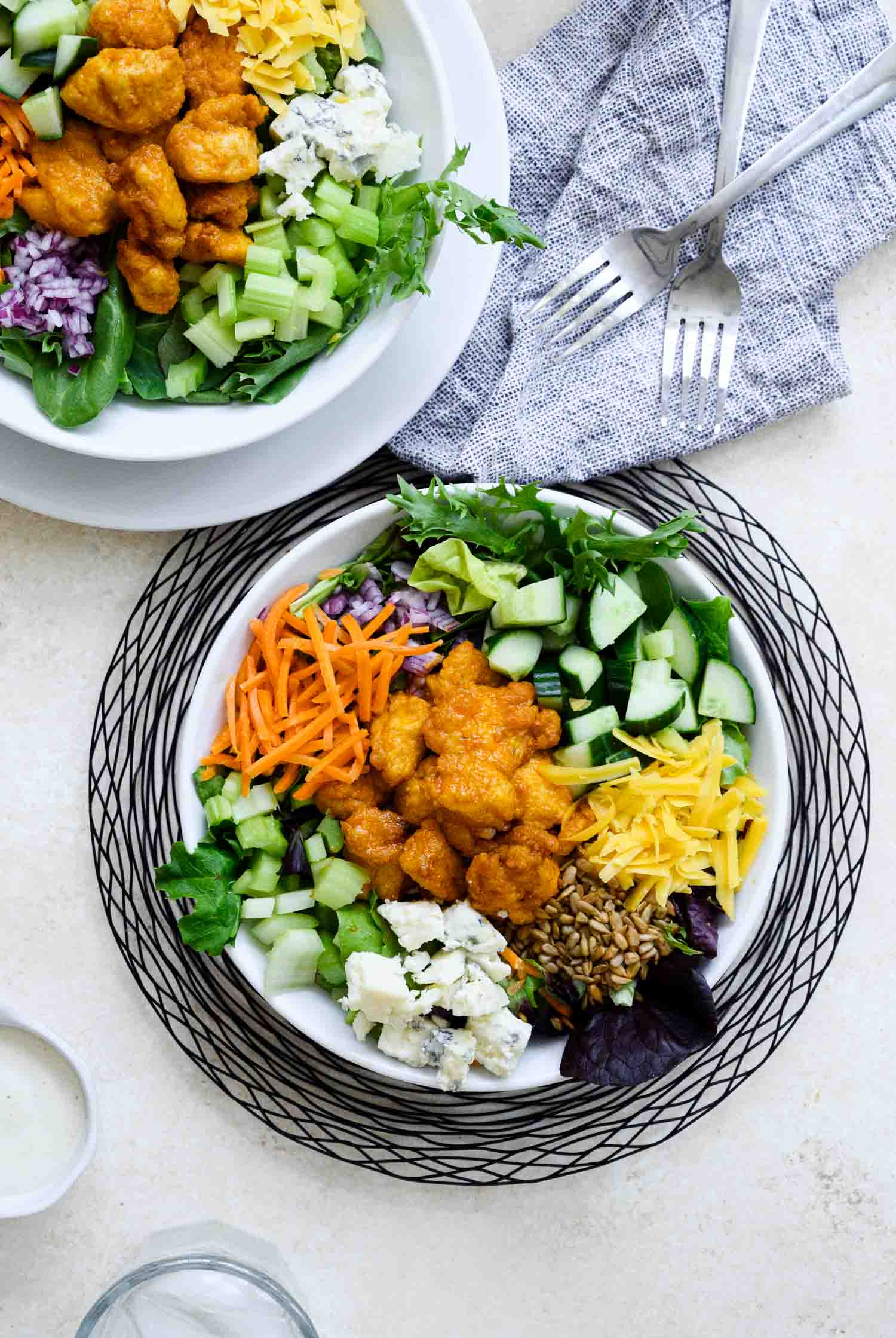 Two white bowls of salad ingredients including some buffalo chicken and crumbled blue cheese