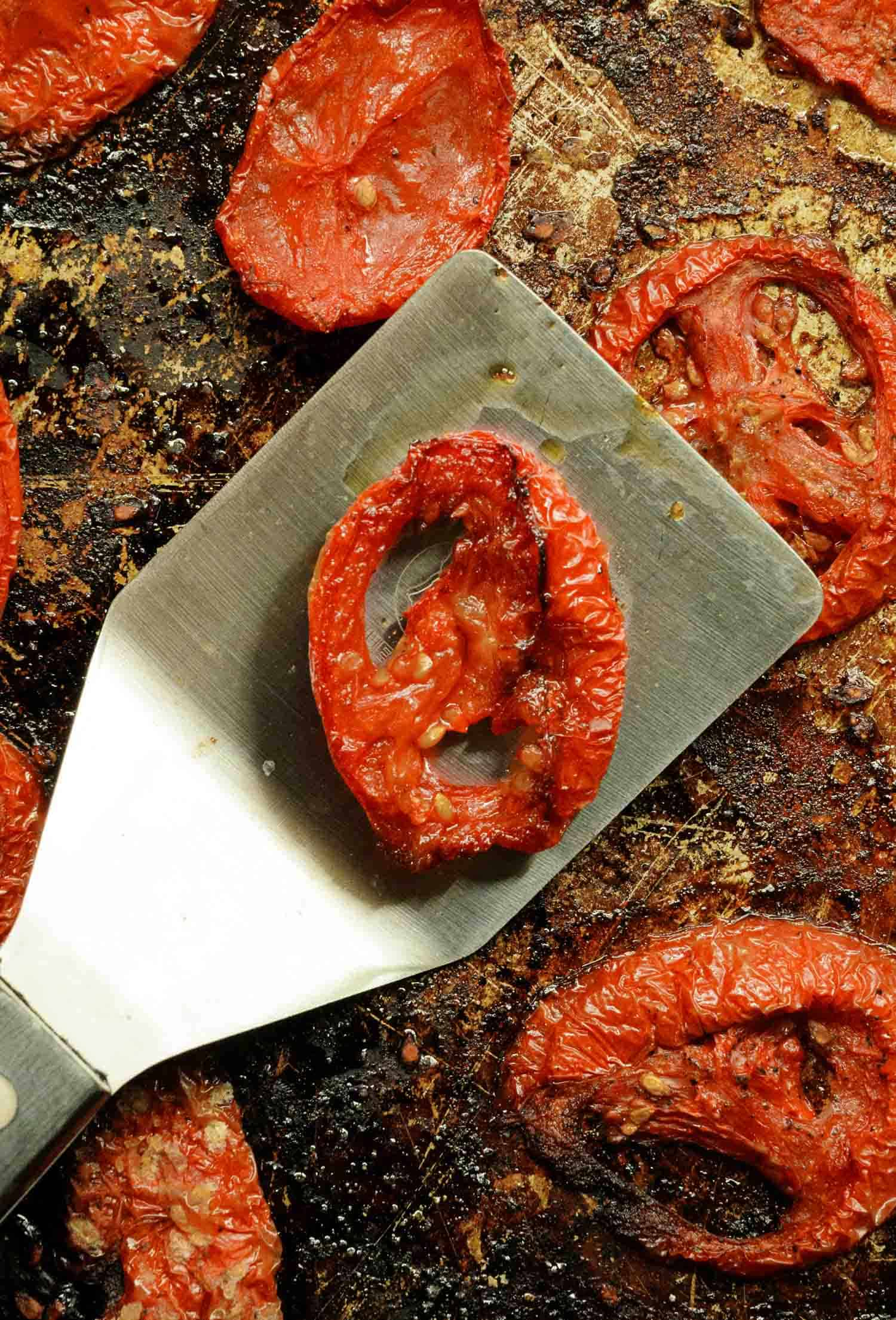 roasted tomatoes on a spatula and a sheet pan
