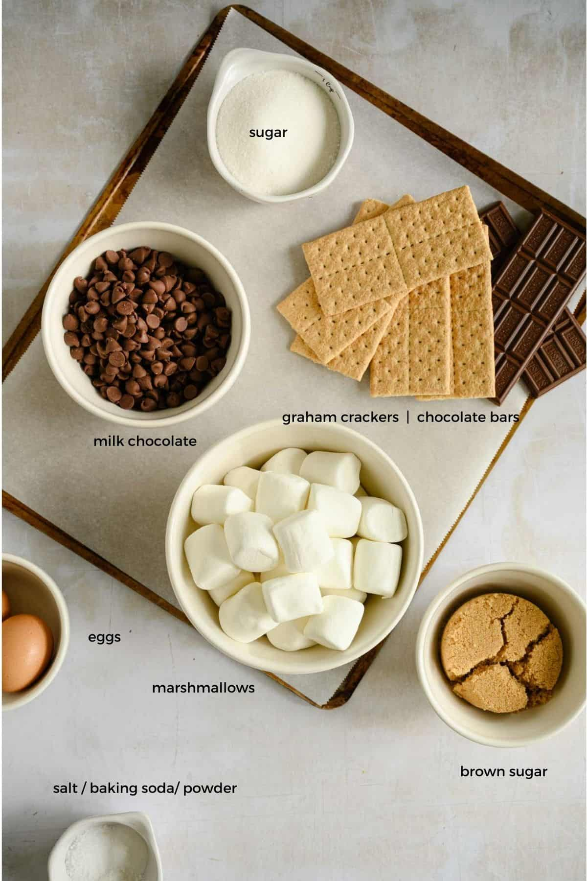 ingredients to make s'mores cookies laid out on a cookie sheet covered with parchment
