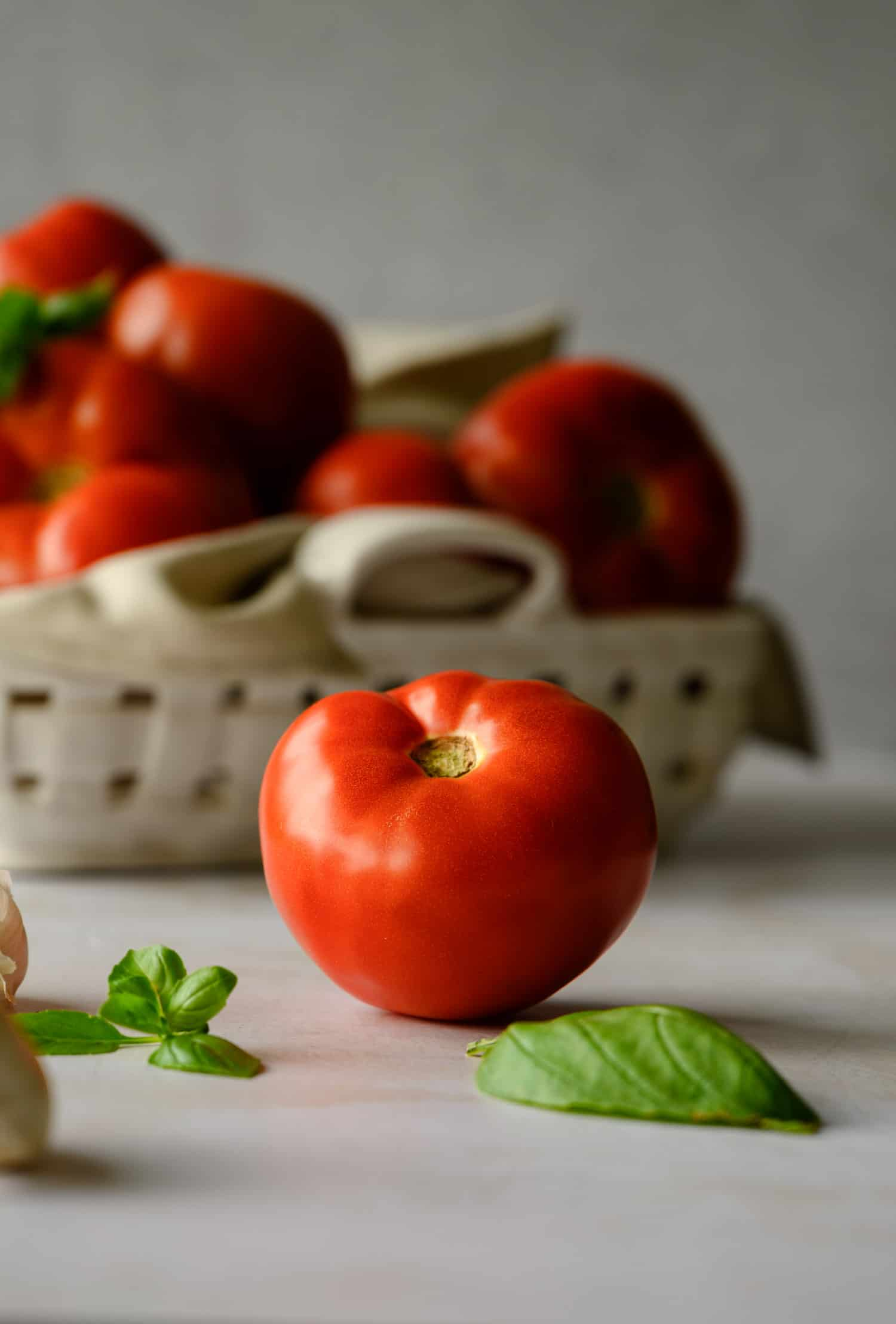 fresh garden tomato on a white background with loose basil leaves and more tomatoes in a white basket