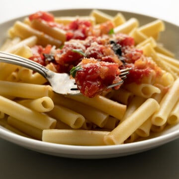 white bowl of ziti pasta with some fresh marinara sauce and a fork in front of a window