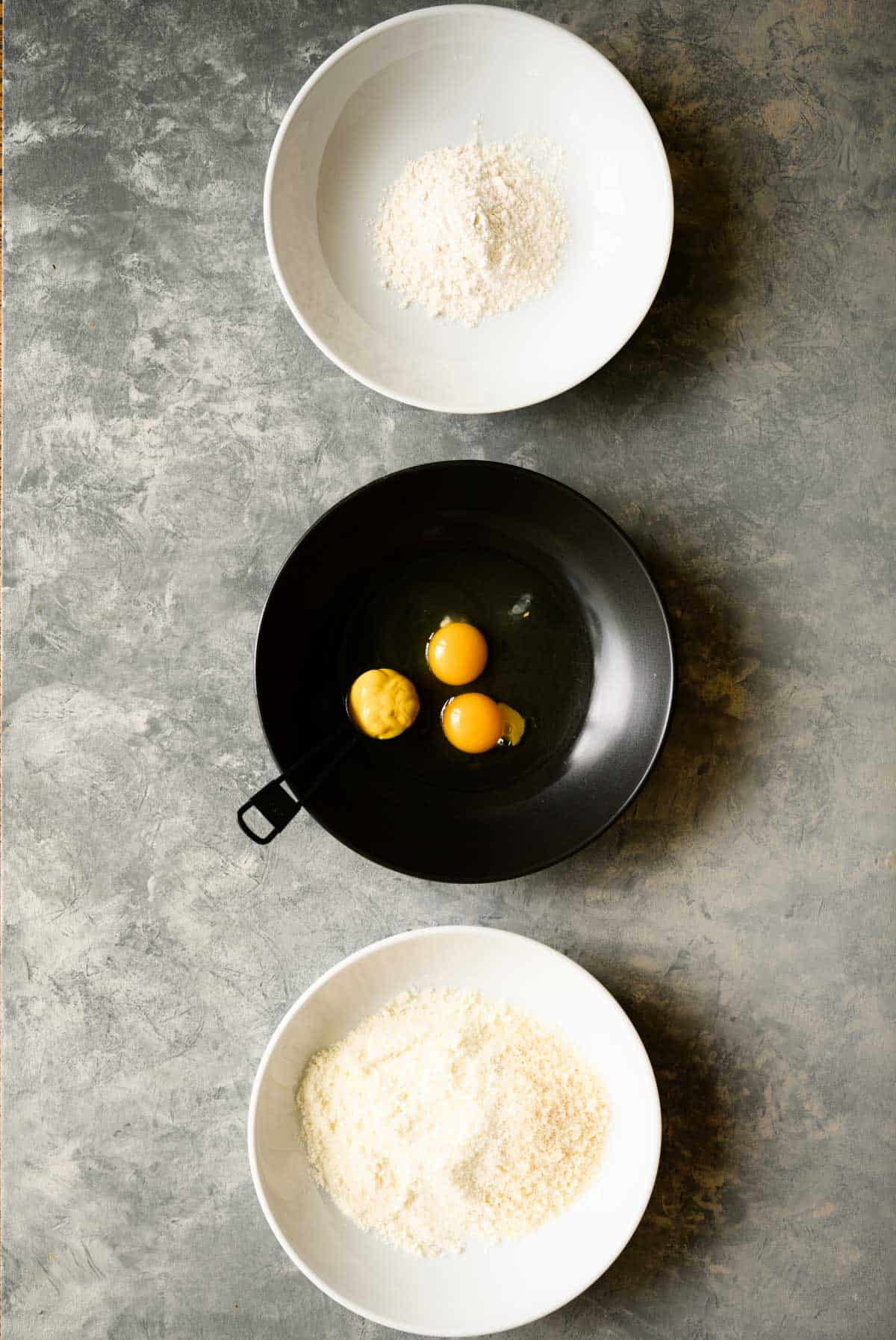 a white bowl with flour, a black bowl with eggs and mustard , and a white bowl of breadcrumbs