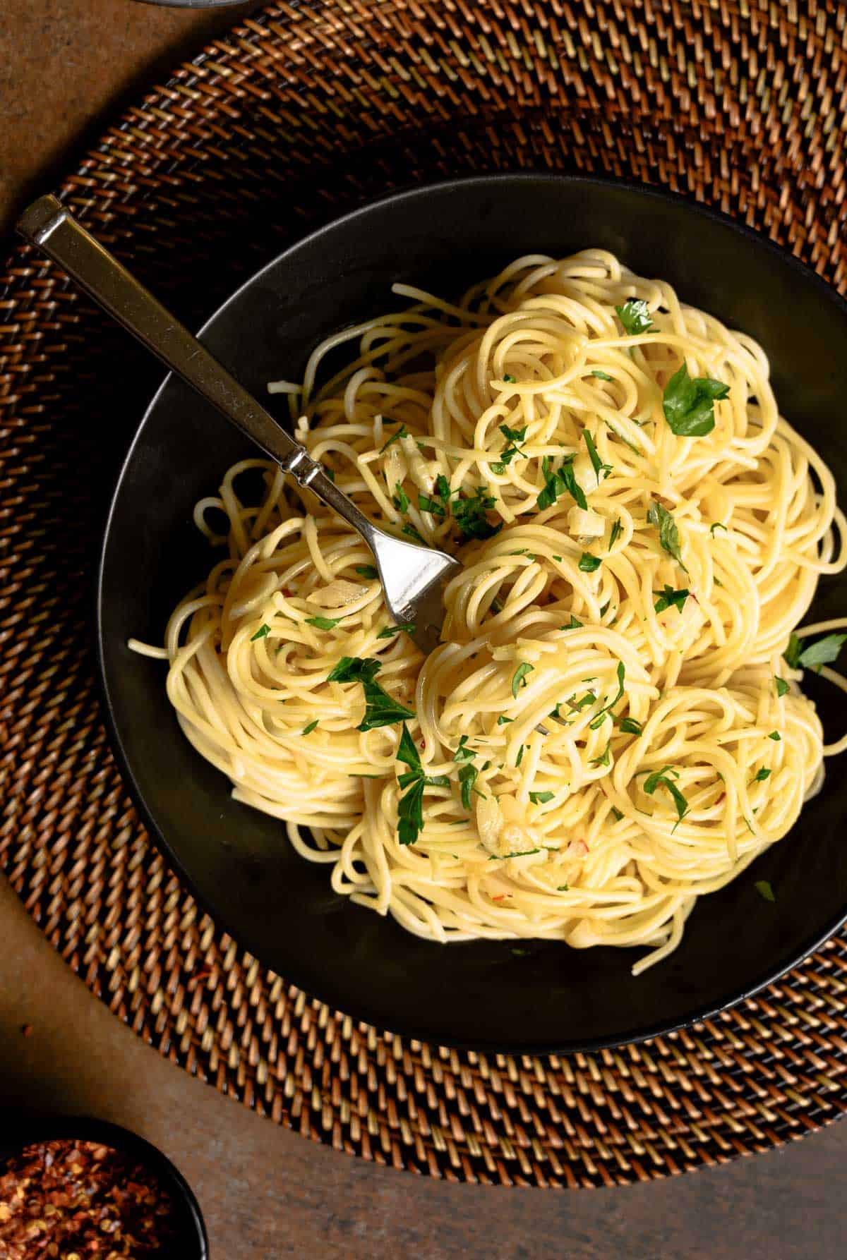black plate of spaghetti and parsley on a rattan charger.