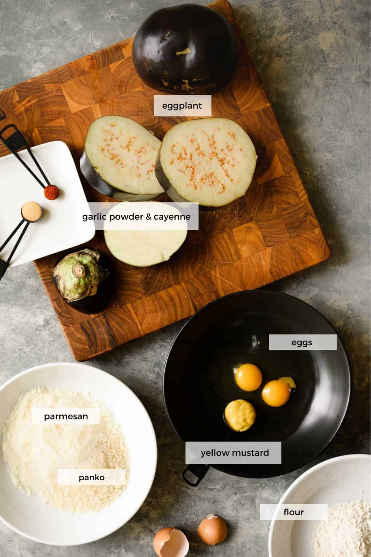 wooden cutting board with slices of eggplant, spoons with seasoning and bowls of eggs, flour, and breading.