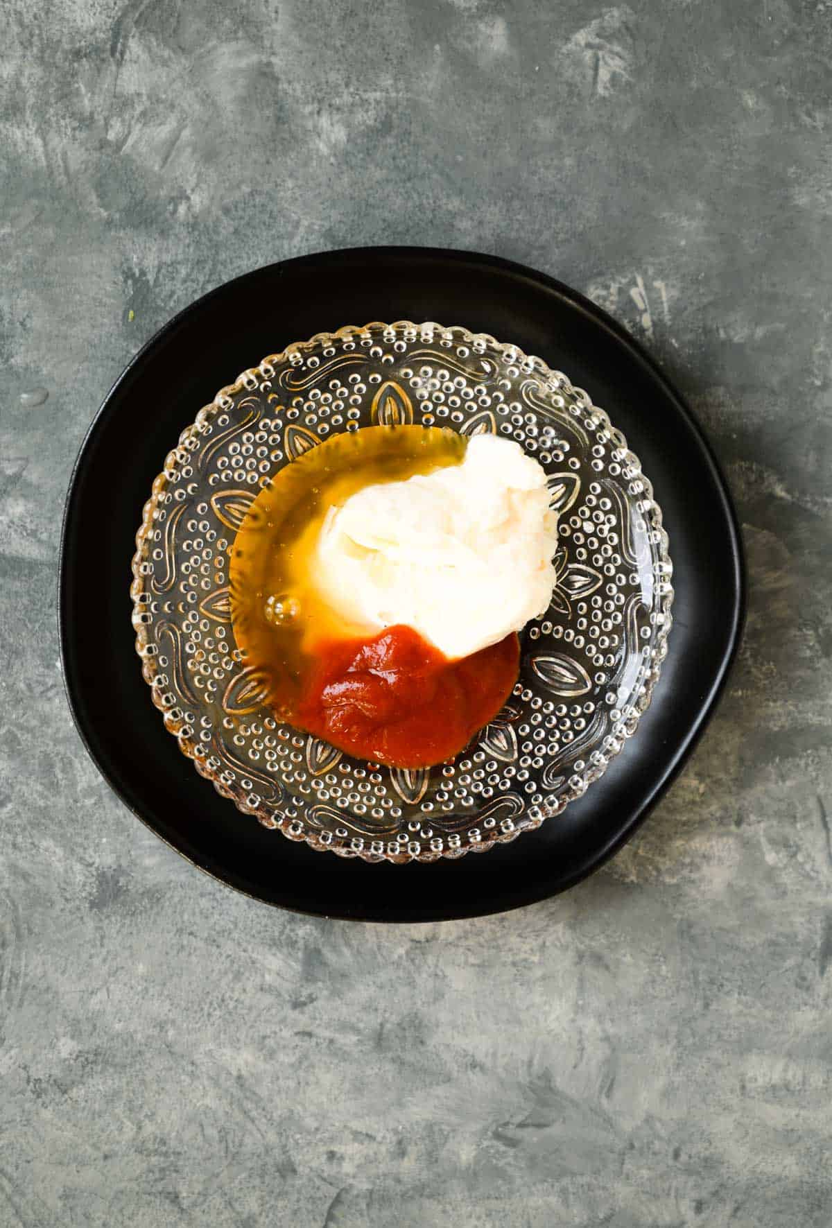 honey, mayonnaise, and sriracha in a cut glass bowl sitting inside a larger black bowl.