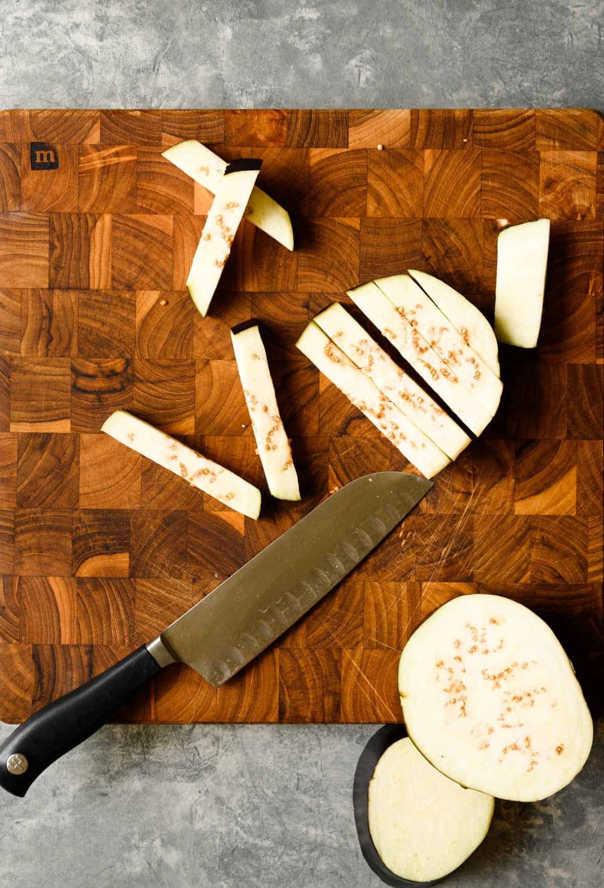 eggplant being sliced into fries on a wooden cutting board.