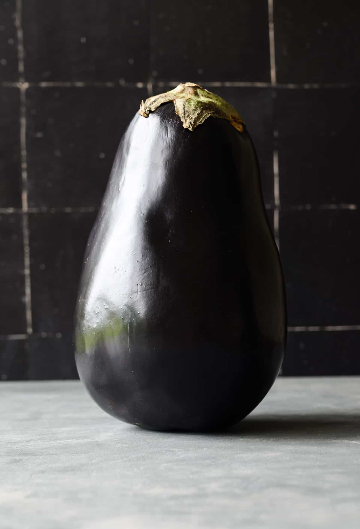 whole eggplant standing on a light gray floor with a black tile background.